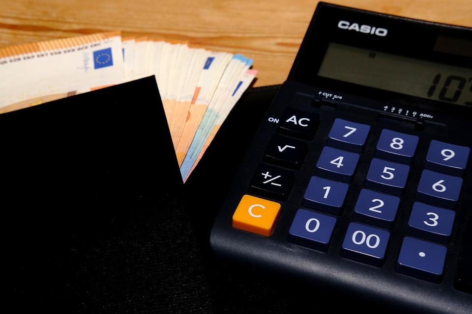 Taschenrechner neben einem Portmonee mit Geldscheinen.