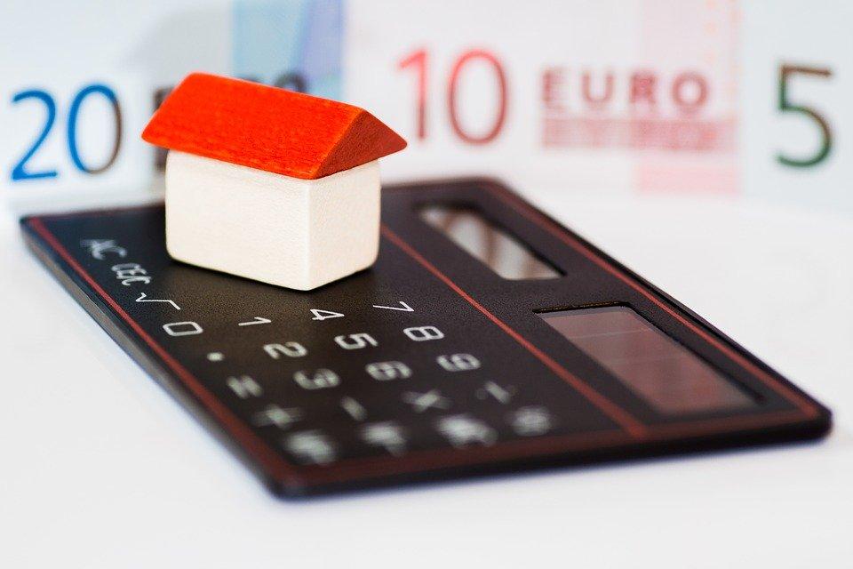 Haus mit Taschenrechner und Geldscheinen.