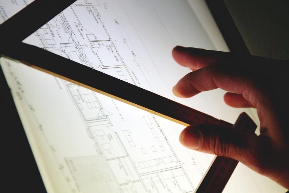 Hand eines Mannes vor dem Bauplan eines Hauses.
